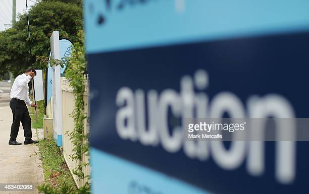 An estate agent puts up signs before the home auction for a fourbedroom house at 230 Blacktown Road on February 14 2015 in Blacktown Australia The...