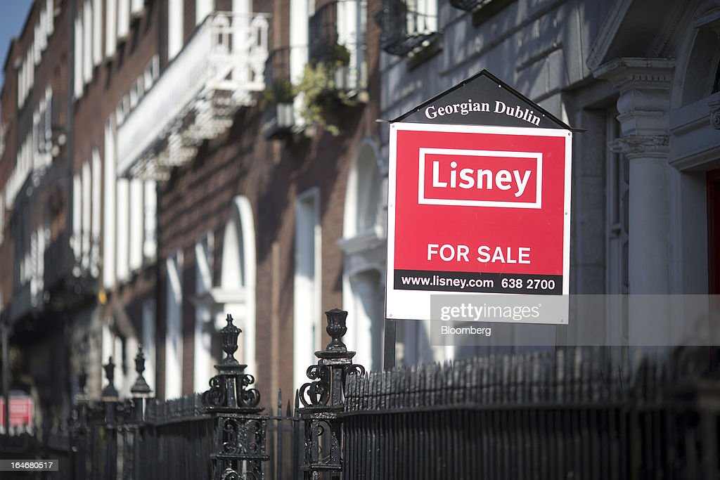 An estate agent's 'For Sale' board sits outside a Georgian house on Merrion Square in Dublin, Ireland, on Saturday, March 16, 2013. Ireland's renewed competiveness makes it a beacon for the U.S. companies such as EBay, Google Inc. and Facebook Inc., which have expanded their operations in the country over the past two years. Photographer: Simon Dawson/Bloomberg via Getty Images