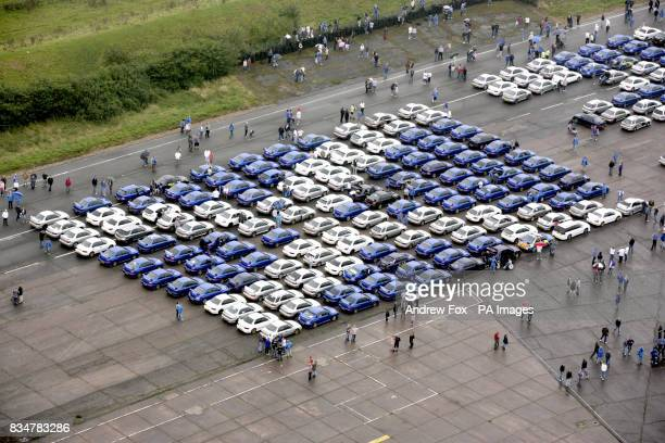 An estimated 1300 Subaru car owners create the Scottish Saltaire Flag at the Prodrive test track in Banbury Oxfordshire to pay tribute to the late...