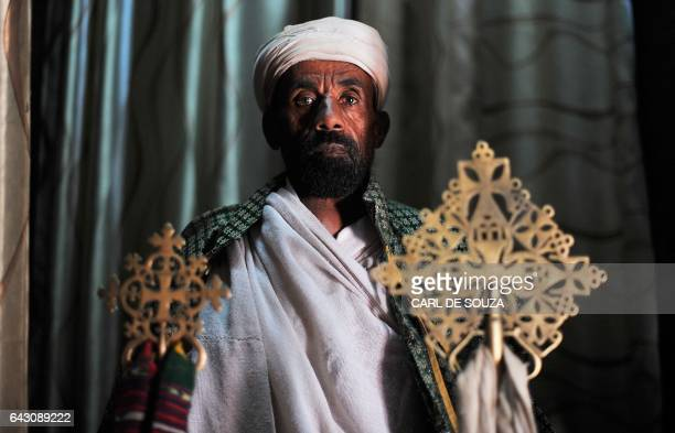 An Ethiopian Orthodox Christian priest poses for a photograph before taking part in celebrations for the annual festival of Timkat in Lalibela on...