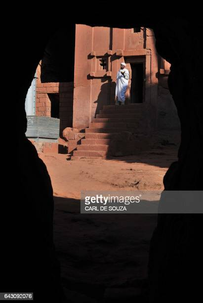 An Ethiopian Orthodox Christian priest stands at the entrance of the rockhewn UNESCO protected Church of Saint Emmanuel where fellow believers gather...