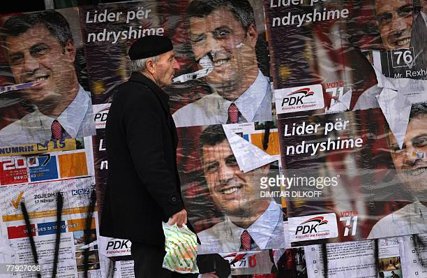 An ethnic Albanian man walks by preelection posters featuring the leader of the Democratic Party of Kosovo Hashim Thaci in Pristina 15 November 2007...