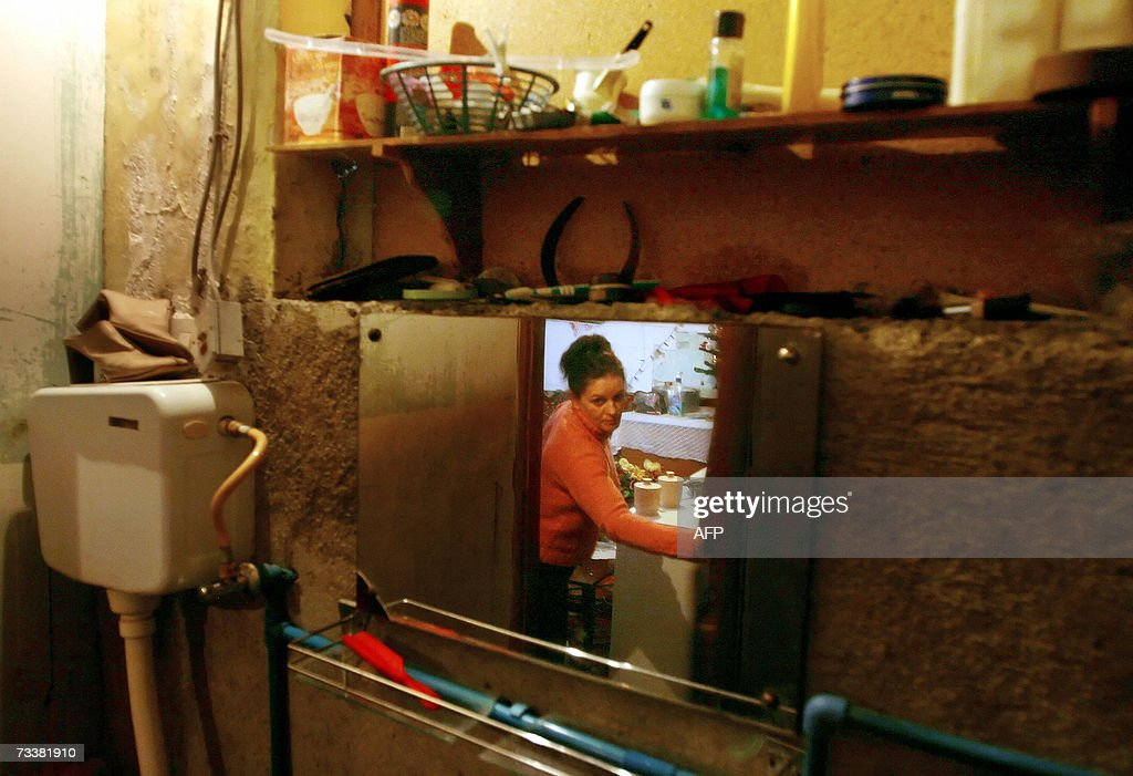 An ethnic Albanian woman is reflected in the mirror of a bathroom at a refugee house in the town of Skenderaj, 21 February 2007. Some 20 familyes living in unbearable conditions at the refugee house in Skenderaj. All of them expect their conditions to improve once the status is settled. Serbian and ethnic Albanian negotiators met in Vienna on Wednesday for a final contentious round of talks on the future status of the breakaway province.