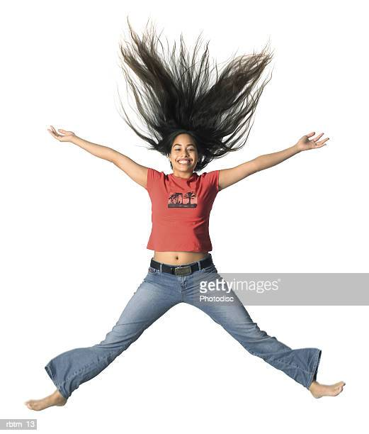 an ethnic female teen in jeans and a red shirt jumps up playfully