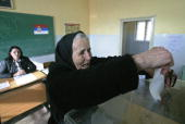 An ethnic Kosovo Serb woman casts her ballot at a polling station in the village of Gracanica 03 February 2008 The Serbian minority in Kosovo voted...