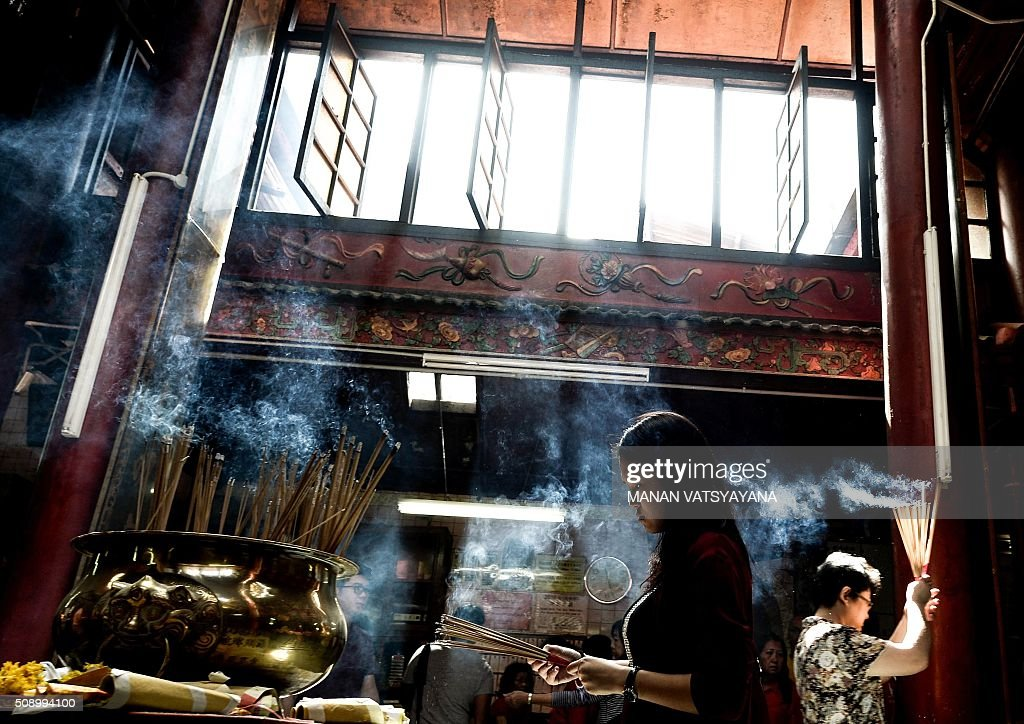 An ethnic Malaysian-Chinese devotee burns incense for good luck at the Guan-Di Temple on the first day of the Lunar New Year in Kuala Lumpur's popular Chinatown area on February 8, 2016. Some 25 percent of Malaysia's 29 million people are ethnic Chinese and celebrate the Lunar New Year, this year marking the Year of the Monkey. AFP PHOTO / MANAN VATSYAYANA / AFP / MANAN VATSYAYANA