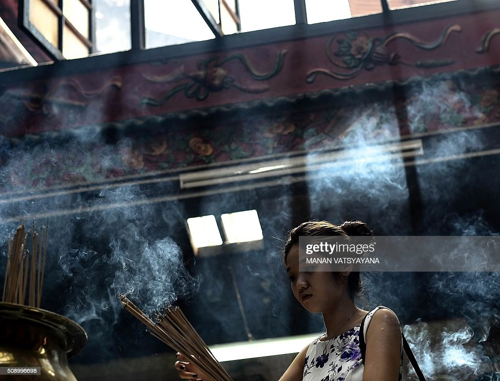 An ethnic Malaysian-Chinese devotee burns incense for good luck at the Sin Sze Si Ya Temple on the first day of the Lunar New Year in Kuala Lumpur's popular Chinatown area on February 8, 2016. Some 25 percent of Malaysia's 29 million people are ethnic Chinese and celebrate the Lunar New Year, this year marking the Year of the Monkey. AFP PHOTO / MANAN VATSYAYANA / AFP / MANAN VATSYAYANA
