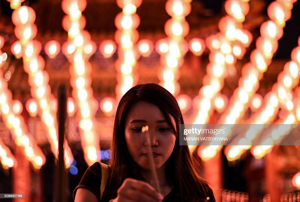An Ethnic Malaysian-Chinese devotee burns joss-sticks at the Thean Hou temple decorated with red lanterns in Kuala Lumpur on February 7, 2016, on the eve of the Lunar New Year. The Lunar New Year will mark the start of the Year of the Monkey on February 8. AFP PHOTO / MANAN VATSYAYANA / AFP / MANAN VATSYAYANA