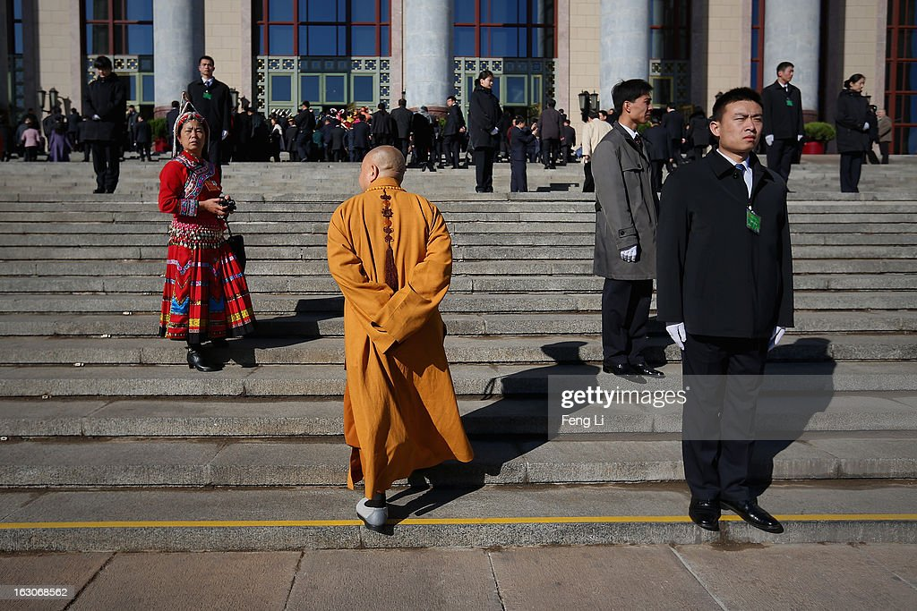 An ethnic minority delegate (L) and a monk delegate (C) walks on the steps to enter the Great Hall of the People before attending a pre-opening session of the National People's Congress, China's parliament, on March 4, 2013 in Beijing, China. China's defensive military policies have played a core role in maintaining peace and stability in Asia, a spokesperson for the annual session of China's national legislature said Monday.