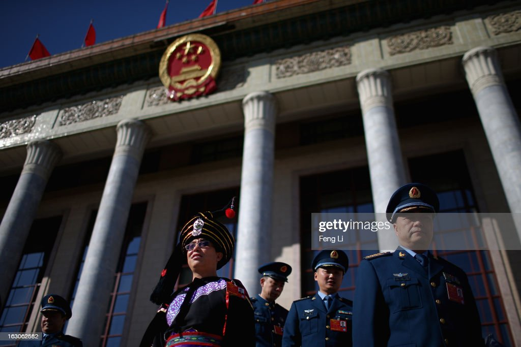 An ethnic minority delegate and Chinese People's Liberation Army delegates walk out the Great Hall of the People after attending a pre-opening session of the National People's Congress, China's parliament, on March 4, 2013 in Beijing, China. China's defensive military policies have played a core role in maintaining peace and stability in Asia, a spokesperson for the annual session of China's national legislature said Monday.