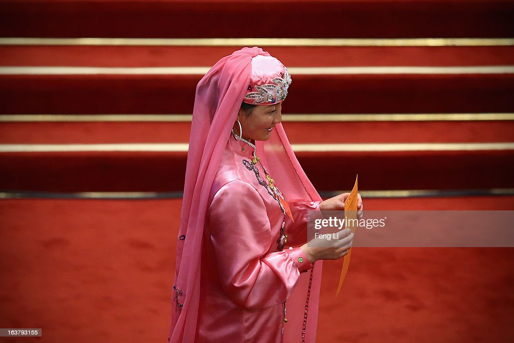 An ethnic minority delegate takes her vote during the sixth plenary meeting of the National People's Congress at the Great Hall of the People on March 16, 2013 in Beijing, China. The new lineup of China's State Council, nominated by Premier Li Keqiang, was endorsed by lawmakers at the ongoing national legislative session Saturday afternoon.