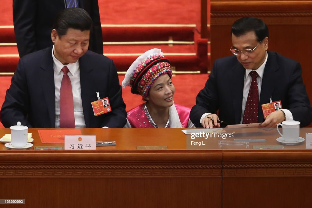 An Ethnic minority (C) gets the newly-elected Chinese President <a gi-track='captionPersonalityLinkClicked' href=/galleries/search?phrase=Xi+Jinping&family=editorial&specificpeople=2598986 ng-click='$event.stopPropagation()'>Xi Jinping</a> (L) and incoming Premier <a gi-track='captionPersonalityLinkClicked' href=/galleries/search?phrase=Li+Keqiang&family=editorial&specificpeople=2481781 ng-click='$event.stopPropagation()'>Li Keqiang</a> (R) to sign an autograph after the election of the new president during the fourth plenary meeting of the National People's Congress at the Great Hall of the People on March 14, 2013 in Beijing, China. <a gi-track='captionPersonalityLinkClicked' href=/galleries/search?phrase=Xi+Jinping&family=editorial&specificpeople=2598986 ng-click='$event.stopPropagation()'>Xi Jinping</a>, general secretary of the Communist Party of China Central Committee, was elected President of the People's Republic of China and Chairman of the Central Military Commission on Thursday.