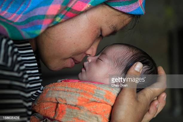 An ethnic minority H'mong woman with her new born baby boy at their house in Chi Ca commune Xin Man district Ha Giang province