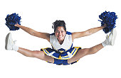 an ethnic teenage female cheerleader jumps high in the air and does the splits