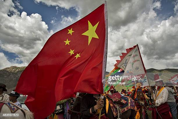 An ethnic Tibetan nomad carries a China flag while waiting to perform skills during a riding competition at a government sponsored local festival on...
