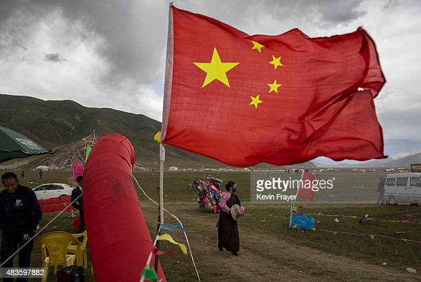 An ethnic Tibetan nomad walks passed a China flag at a carnival on July 25 2015 at a local government sponsored festival on the Tibetan Plateau in...