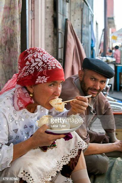 An ethnic Uighur woman eating samsa stuffed meat pies in Kashgar in Xinjiang Province in China The Uighurs are a Turkic ethnic group living in...
