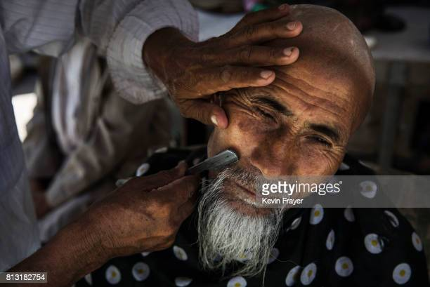 An ethnic Uyghur man has his beard trimmed after prayers on June 30 2017 in the old town of Kashgar in the far western Xinjiang province China...