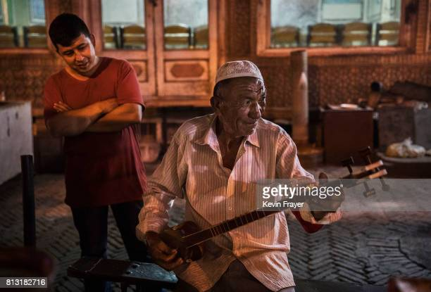 An ethnic Uyghur man players a local instrument at his food stall early on July 1 2017 in the old town of Kashgar in the far western Xinjiang...