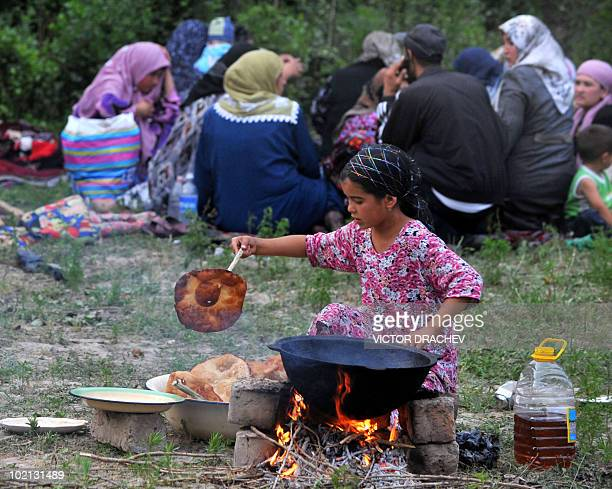 An ethnic Uzbek girl prepares food in a refugee camp outside the village of Begabad some 30 kilometres south from DzhalalAbad on June 15 2010 on the...