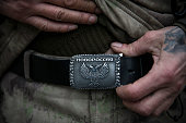 An ethnically Cossack proRussian rebel displays a belt buckle that says 'New Russia' at a firing range on March 12 2015 in Donetsk Ukraine The...