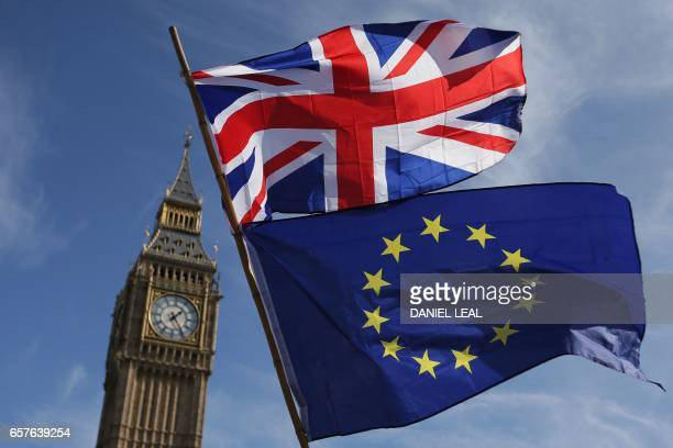 TOPSHOT An EU flag and a Union flag held by a demonstrator is seen with Elizabeth Tower and the Houses of Parliament as marchers taking part in an...