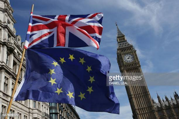 An EU flag and a Union flag held by a demonstrator is seen with Elizabeth Tower and the Houses of Parliament as marchers taking part in an antiBrexit...