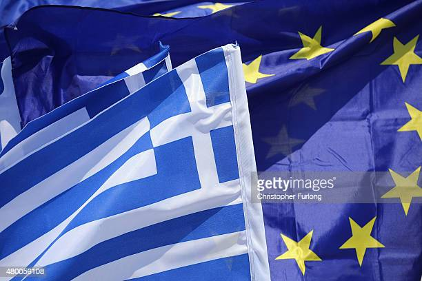 An EU flag and flags of Greece flutter in the wind on a street vendors stall on July 9 2015 in Athens Greece The Greek government has hours left to...