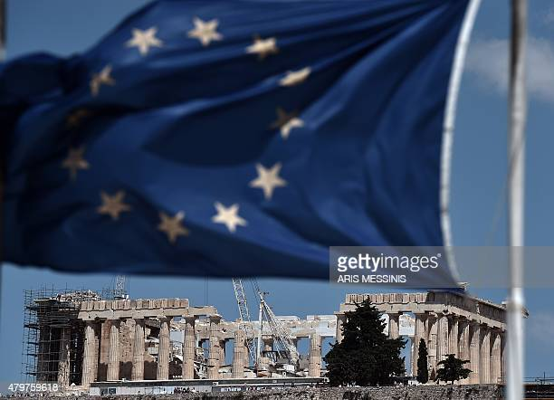 An EU flag waves above the ancient temple of Parthenon atop the Acropolis hill in Athens on July 7 2015 Eurozone leaders will hold an emergency...