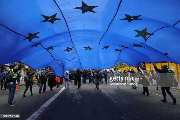 An European Union flag is held up as people take part in antiBrexit and antiausterity protests as the Conservative party annual conference gets...