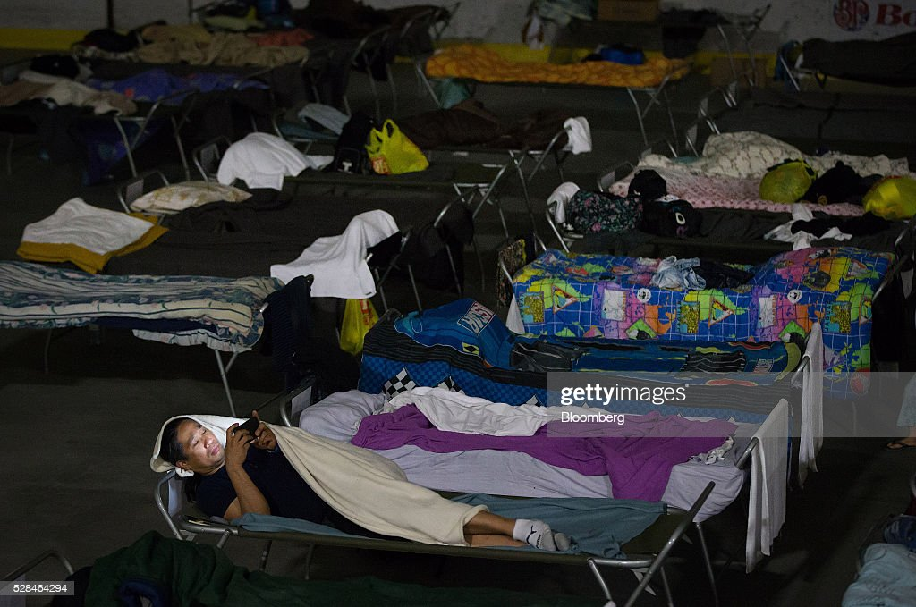 An evacuee from wildfires in the Fort McMurray area lies on a cot at a hockey rink in Lac La Biche, Alberta, Canada, on Thursday, May 5, 2016. A fire fueled by shifting winds that forced more than 80,000 people to flee their homes and threatened the business district of oil-sands hub Fort McMurray, Canada, raged out of control Wednesday after consuming 80 square kilometers (30 square miles) of land and damaging 1,600 buildings. Photographer: Darryl Dyck/Bloomberg via Getty Images