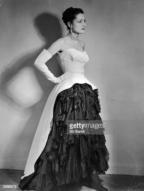 An evening dress designed by Cristobal Balenciaga with crisp white cotton pique cut away at the front to show a full skirt of soft black silk...