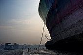 An evening sunset scene of a mega freighter that is out of service and has been left on Chittagong beach to be disassembled by poor laborers Where do...