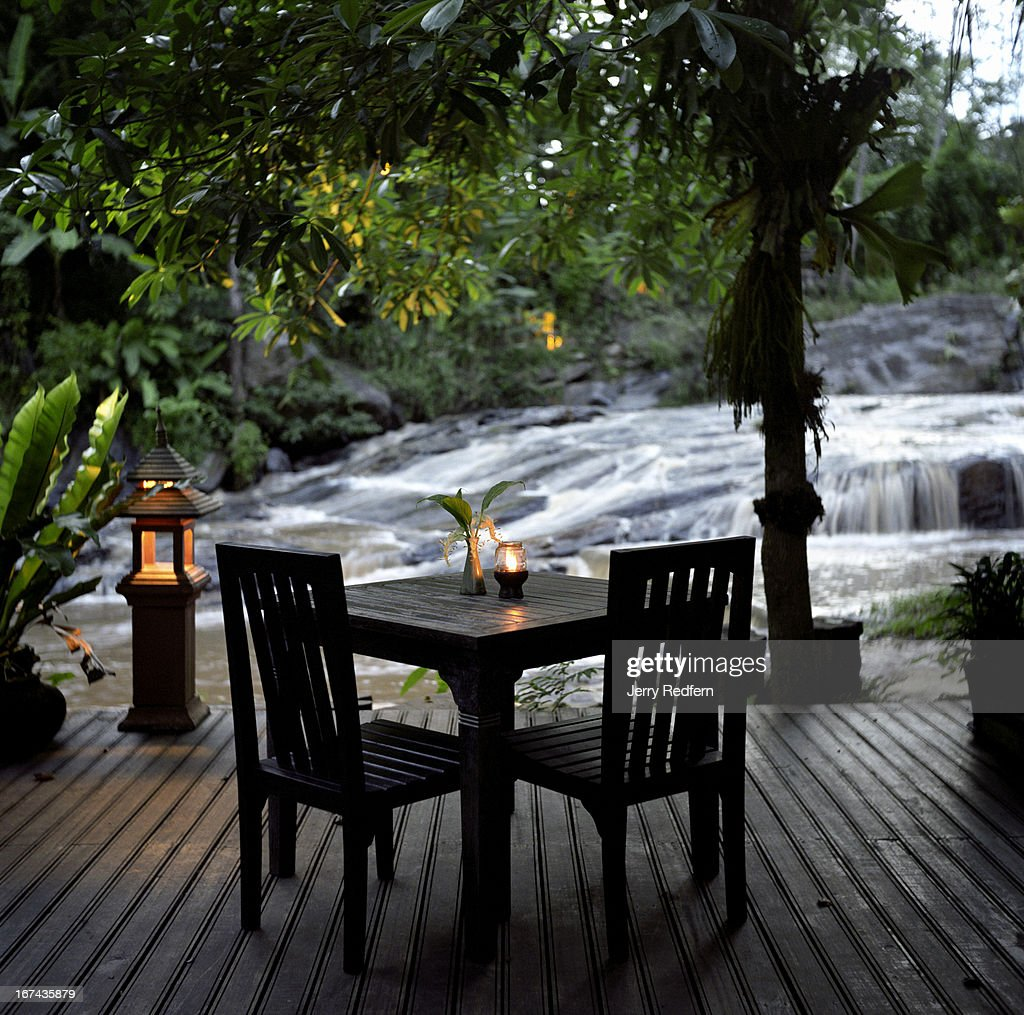 An evening view of the dining area overlooking the creek that bisects the Sukantara Cascade Resort property. The Thai jungle covers the side of the creek opposite the resort, located in the hills an hour's drive from Chiang Mai. The resort features individual attention, posh rooms with Thai trimmings in wood and silk and a beautiful location on a cascading stream. Angelina Jolie stayed here in 2004..