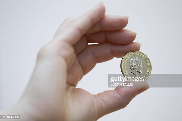 An event assistant shows the new coin portrait of Britain's Queen Elizabeth II on a two pound coin at the National Portrait Gallery in London on...