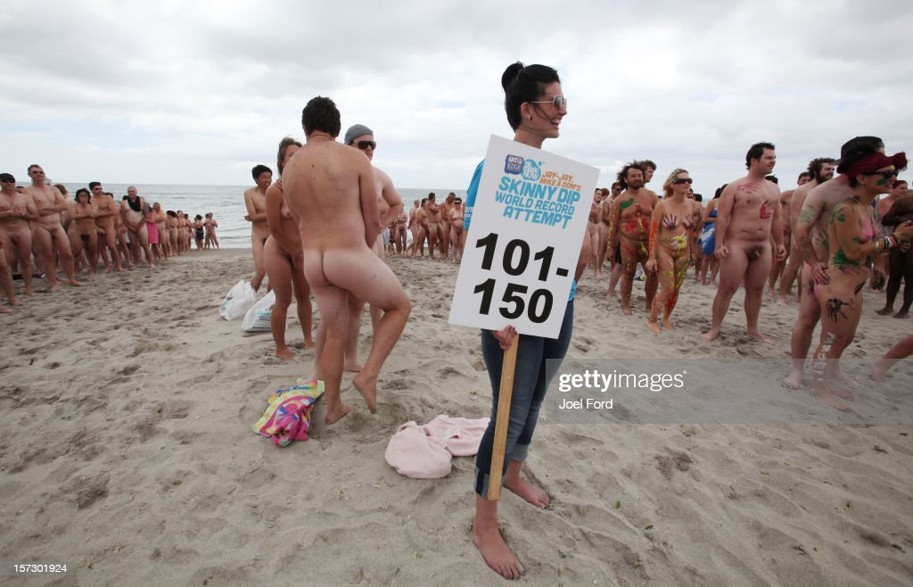 An event organizer from a local radio station holds a placard showing where the 101st to 150th people are lined up during an attempt to break the skinny dip world record at Papamoa Beach on December 2, 2012 in Tauranga, New Zealand.