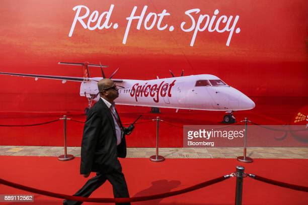 An event staff walks past an advertisement for SpiceJet Ltd during an event in Mumbai India on Saturday Dec 9 2017 SpiceJet an Indian budget carrier...