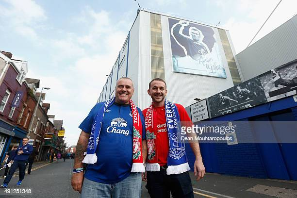 An Everton and Liverpool fan pose for a photo outside the stadium ahead of the Barclays Premier League match between Everton and Liverpool at...