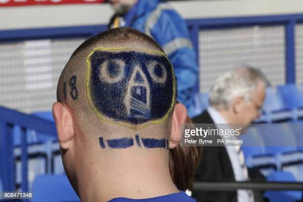 An Everton suppporter who has their emblem shaved onto the back of his head in the stands