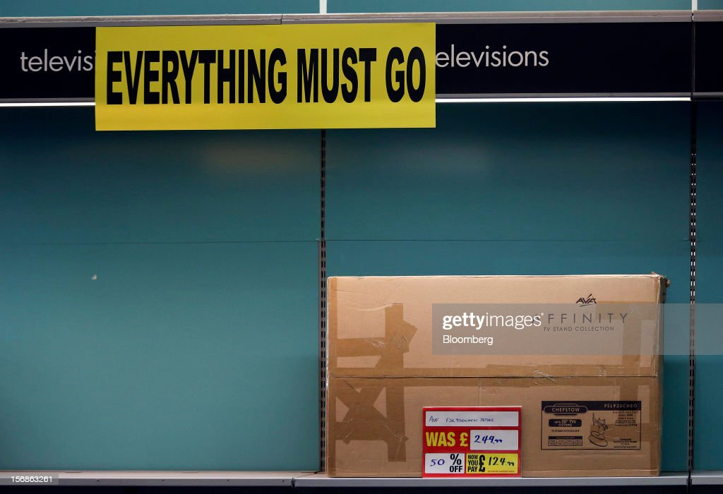 An 'Everything Must Go' sign hangs above a half-price flat-screen television stand inside a Comet electronics store in Slough, U.K., on Friday, Nov. 23, 2012. Comet, a U.K. electronics chain, appointed Deloitte LLP as insolvency administrator, less than a year after being bought by private-equity firm OpCapita LLP. Photographer: Chris Ratcliffe/Bloomberg via Getty Images