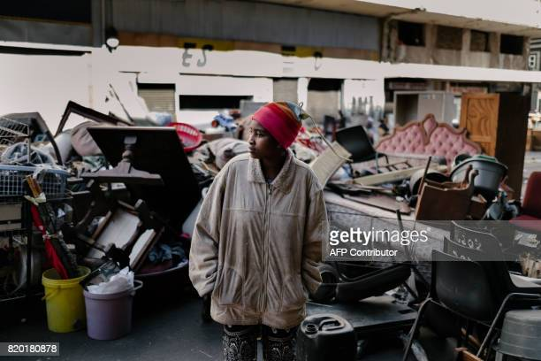 An evicted resident of Fattis Mansion in Johannesburg stands among the scattered belongings on July 21 2017 Residents of the allegedly illegally...