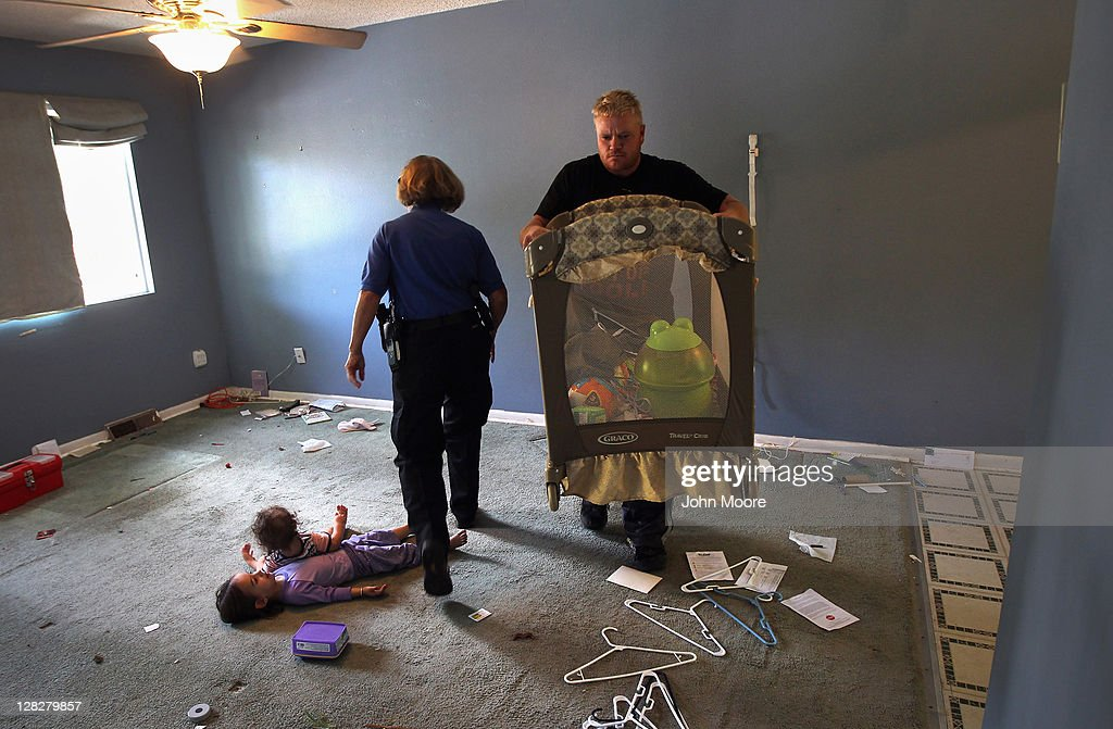 An eviction team member removes a playpen from a house as a sheriff's deputy steps over children during a home foreclosure on October 5, 2011 in Milliken, Colorado. The owners had stopped making mortgage payments some 11 months before, and the bank took possession of their home after receiving a court order. The family's possessions were removed to the front yard and the door locks changed. A nationwide glut of foreclosed homes is expected to depress U.S. housing values for years.