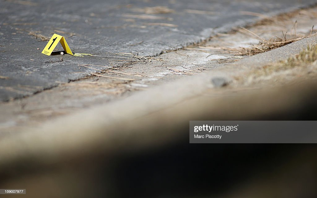 An evidence marker next to a round of ammunition in the street in front of a town home where four people were killed Saturday morning including the gunman who held police at bay for several hours at the complex January 5, 2013 in Aurora, Colorado. Aurora SWAT team members shot a gunman after he went to a second-floor window and fired at police. The gunman also allegedly fatally shot two men and a woman that he had taken hostage. One woman managed to escape from an upstairs back window, ran from the home and called police just before 3 a.m., said Cassidee Carlson, Aurora police spokeswoman.