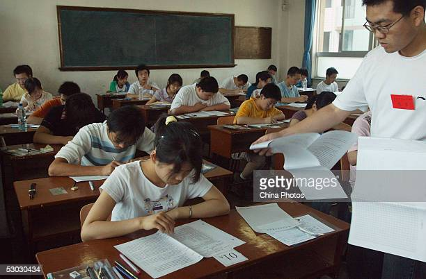 An examiner hands out papers to students during the college entrance exam at an exam room in a middle school on June 7 2005 in Xian of Shaanxi...