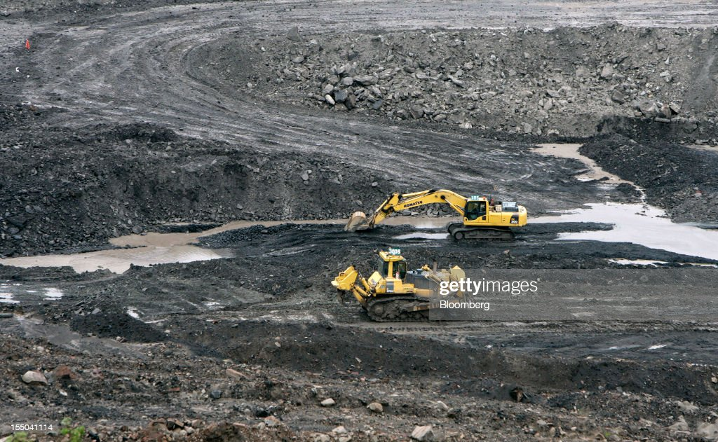 An excavator and a bulldozer operate in the open pit coal mine at the PT Exploitasi Energi Indonesia operations in Asam-Asam, South Kalimantan, Indonesia, on Monday Oct. 29, 2012. Indonesia, the world's largest exporter of coal for electricity generation, will reduce the amount of the fuel that producers must sell to buyers inside the country for next year by 9.4 percent. Photographer: Dadang Tri/Bloomberg via Getty Images