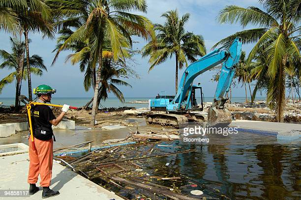 An excavator and a South Korean rescue worker empty a pool in the Khao Lak resort area on Phuket Island in southern Thailand Sunday January 2 2005...