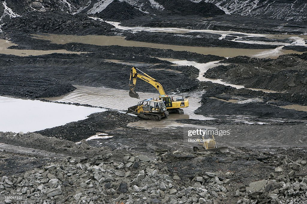 An excavator and bulldozers operate in the open pit coal mine at the PT Exploitasi Energi Indonesia operations in Asam-Asam, South Kalimantan, Indonesia, on Monday Oct. 29, 2012. Indonesia, the world's largest exporter of coal for electricity generation, will reduce the amount of the fuel that producers must sell to buyers inside the country for next year by 9.4 percent. Photographer: Dadang Tri/Bloomberg via Getty Images