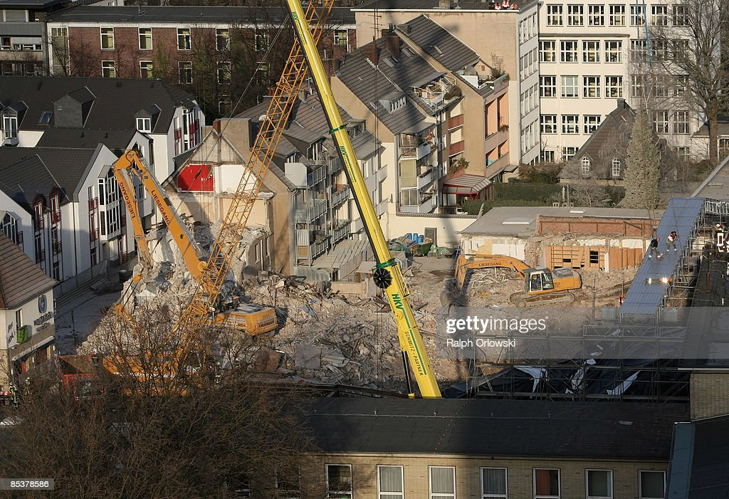 An excavator breaks down the ruin of a house standing next to the wrecked building of the Historical Archive of the City of Cologne on March 11, 2009 in Cologne, Germany. Cologne's six-story city archive building collapsed on Tuesday, March 3.The archive building dragged down parts of two adjacent buildings that contained apartments and an amusement arcade. Cologne holds archive material going back over centuries, including manuscripts by communist pioneers Karl Marx and Friedrich Engels and documents related to German writer Heinrich Boell.