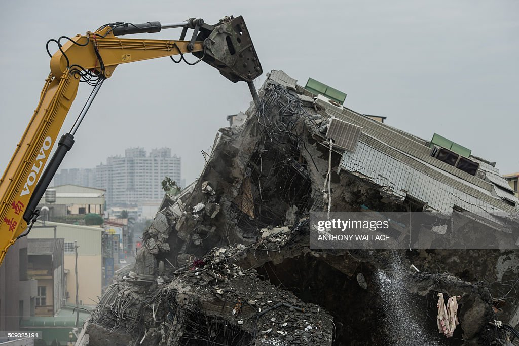 An excavator breaks open the remains of apartments during the search and rescue operation at the Wei-Kuan complex which collapsed in the 6.4-magnitude earthquake, in the southern Taiwanese city of Tainan on February 10, 2016. Taiwan prosecutors were on February 10 questioning the developer of the apartment complex that collapsed during the earthquake as prosecutors detailed flaws in construction of the building where nearly 100 people remain trapped. AFP PHOTO / ANTHONY WALLACE / AFP / ANTHONY WALLACE