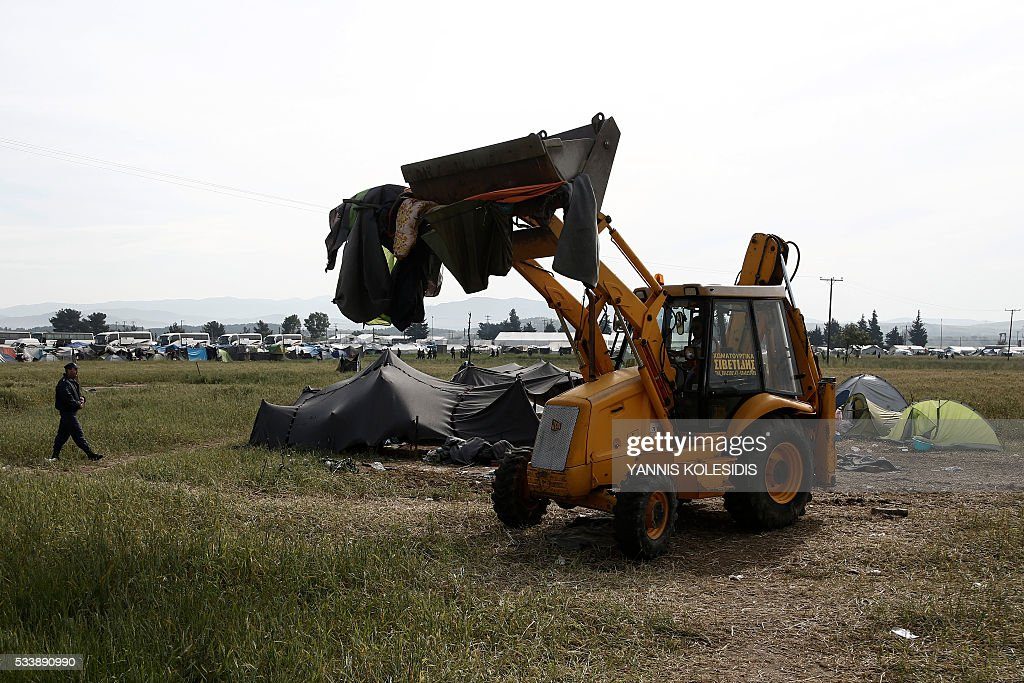 An excavator collects tents during an evacuation operation by police forces of a makeshift migrant camp at the border at the Greek-Macedonian border near the village of Idomeni, on May 24, 2016. In an operation which began shortly after sunrise on May 24, hundreds of Greek police began evacuating the sprawling camp which is currently home to 8,400 refugees and migrants, among them many families with children, an AFP correspondent said. At its height, there were more than 12,000 people crammed into the site, many of them fleeing war, persecution and poverty in the Middle East and Asia, with the camp exploding in size since Balkan states began closing their borders in mid February in a bid to stem the human tide seeking passage to northern Europe. / AFP / POOL / YANNIS